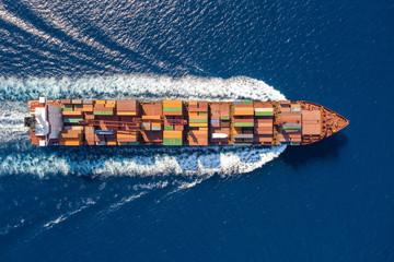 Top down Ansicht auf ein beladenes Containerschiff in voller Fahrt über blauem Meer