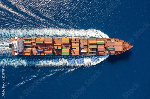 Top down Ansicht auf ein beladenes Containerschidd in voller Fahrt über blauem Meer
