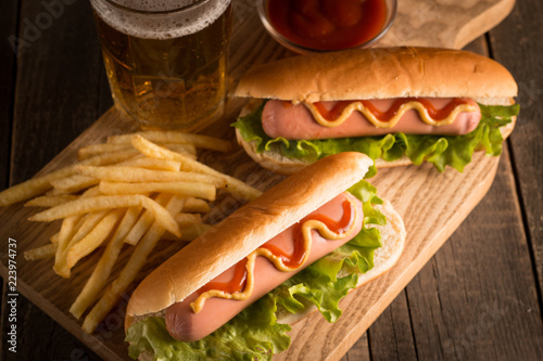 Photo of barbecue grilled hot dog with yellow mustard and ketchup on wooden background. Hot dog sandwich with potato fries and sauces.