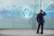 Businessman in front of a wall with bulb lamp idea concept icon on a futuristic interface