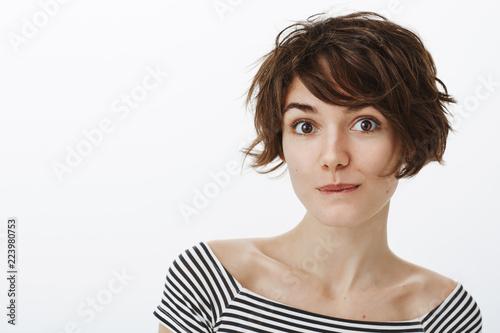 Dreamy good-looking feminine girl with short stylish haircut, smiling and smirking while gazing flirty at camera, expressing positive attitude, being amused with nice talk with guy during date