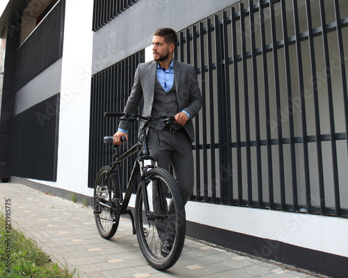 Valokuva  Confident young businessman walking with bicycle on the street in town