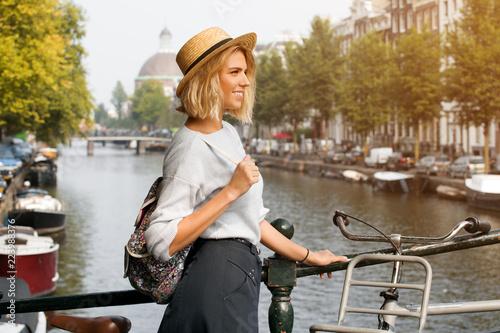 Fototapeta premium Dziewczyna szczęśliwy podróżnik korzystających z miasta Amsterdam. Uśmiechnięta kobieta, patrząc z boku na kanał Amsterdamu, Holandia, Europa