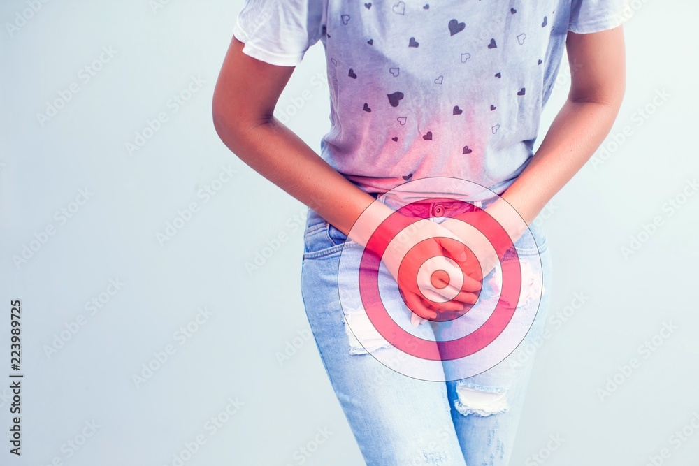 Fototapeta Young sick woman with hands holding pressing her crotch lower abdomen. Medical or gynecological problems, healthcare concept
