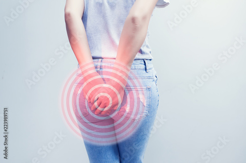 Woman hand holding her bottom because having Abdominal pain and Hemorrhoids, Health care concept Canvas Print