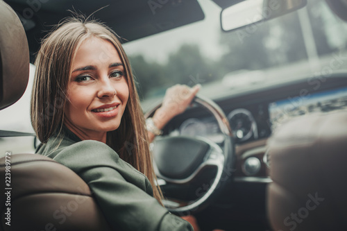Fototapeta Portrait of optimistic pretty girl holding steering wheel while looking at camera. She locating in vehicle obraz
