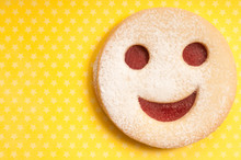 Home Made Linzer Cookie Filled With Jam And Shaped As A Smiley Over Yellow Background