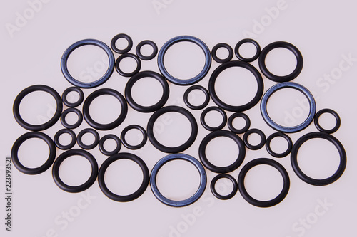 Fotomural Black hydraulic and pneumatic o-ring seals of different sizes scattered a white background