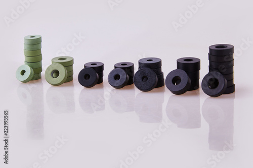 Fototapeta Black and green hydraulic and pneumatic o-ring seals of different sizes stacked on a white background. Rubber rings. Sealing gaskets for hydraulic joints. Rubber sealing rings for plumbing. obraz