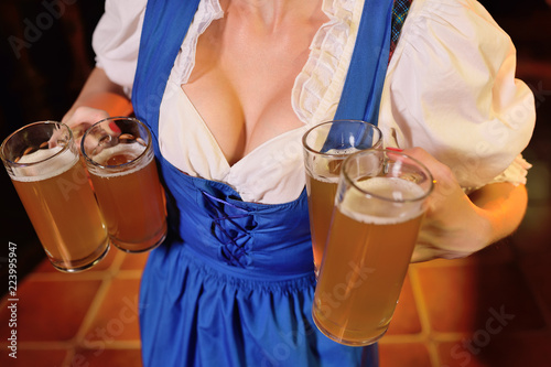 a sexy waiter girl with a big chest in Bavarian clothes holding a lot of beer mugs in the background of the bar during the celebration of the Oktoberfest