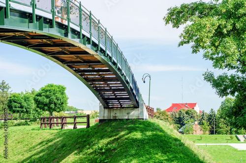 Arched bridge between two green hills