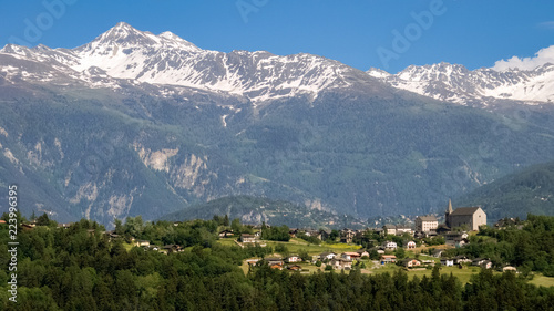 Fototapeta Looking towards the village of Lens on a sunny June day, located in the district
