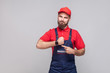 We do ontime. Young confident handyman with beard in blue overall and red t-shirt standing and showing time on his wrist watch with smile. Grey background, indoor, studio shot, isolated