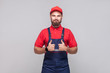 Work are done! Portrait of young satisfied cheerful repairman with beard in blue overall, red t-shirt and cap, standing and showing thumps up with smile. Grey background, indoor studio shot isolated.