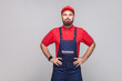 canvas print picture - Portrait of young confident repairman with beard in blue overall, red t-shirt and cap standing and holding hands on waist with smile, indoor, studio shot, isolated on gray background, copy space.