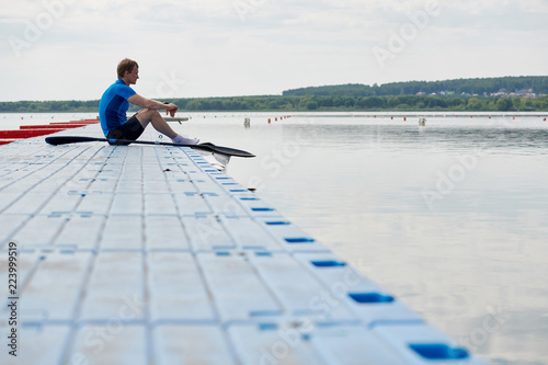 Valokuva  Young kayaker sitting on the pier with kayak and paddle and waiting for rowing c