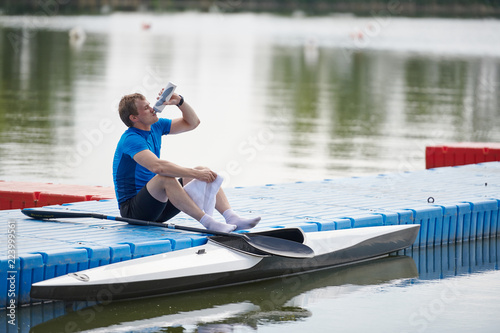 Valokuvatapetti Young sportsman sitting on pier and drinking water from bottle, he resting after