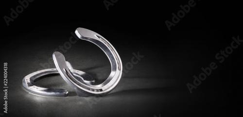 Aluminium Hufeisen edel und silber glänzend auf schwarzem Hintergrund