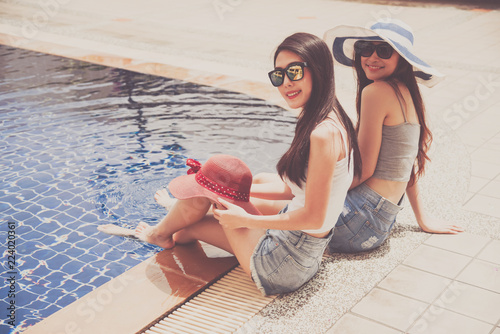 Photo  two women wearing jeans shorts are sitting by the pool