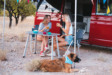 Couple Of Women Friends With Her Dog On A Road Trip Having A Funny Picnic Together A Red Camper Van. Best Friend.