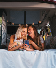 Attractive Women Lying In A Camper Van Enjoying Together With Her Mobile Phone. Road Trip. Best Friend.
