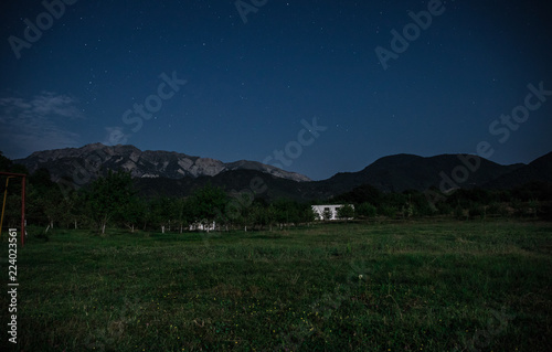 Spoed Foto op Canvas Nachtblauw Mountain night landscape of building at forest at night with moon or vintage country house at night with clouds and stars. Summer night.