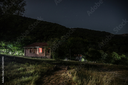 Foto op Canvas Zwart Mountain night landscape of building at forest at night with moon or vintage country house at night with clouds and stars. Summer night.