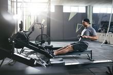 Cardio Training. Sports Man Exercising On Rowing Machine At Gym