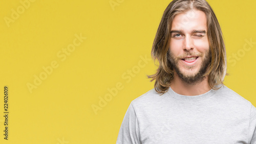Fotografía  Young handsome man with long hair over isolated background winking looking at the camera with sexy expression, cheerful and happy face