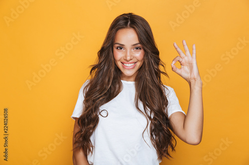 Foto auf Leinwand Friseur Woman isolated over yellow background showing okay gesture.