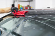 A man cleaning car with microfiber cloth, car detailing (or valeting) concept. Selective focus. Car detailing. Cleaning with sponge. Worker cleaning. Microfiber and cleaning solution to clean