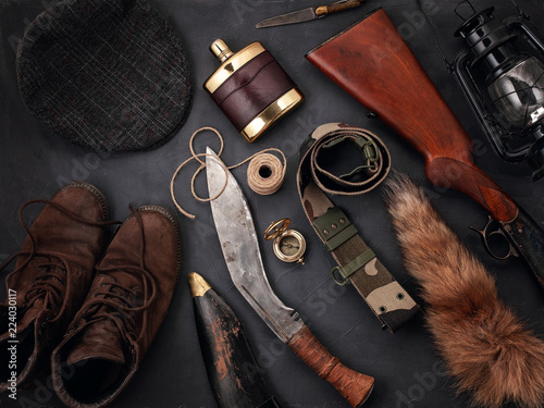Flat lay with hunting accessoties over the grey background: old boots, hat, rifle, knives, rope, belt, fox tail.