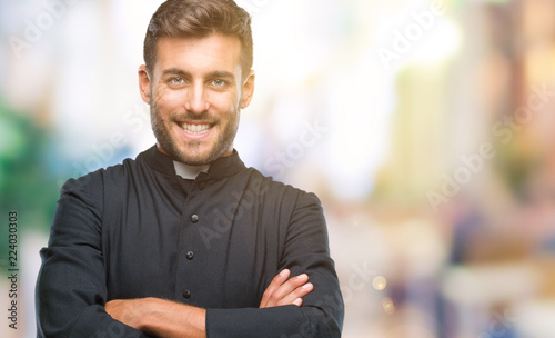 Cuadros en Lienzo Young catholic christian priest man over isolated background happy face smiling with crossed arms looking at the camera