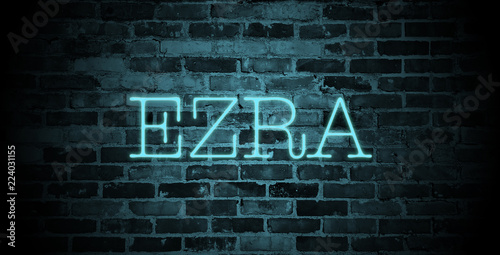 Photo  first name Ezra in blue neon on brick wall