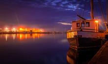 Heavy Clouds Above Tallinn, Pirita. Night Illumination, Reflections Boat Moored At The Small Marina Of Estonia.
