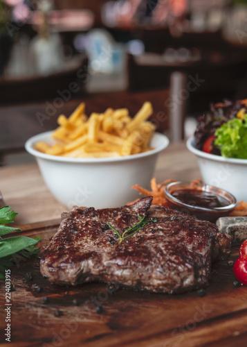 Fotografie, Obraz  Rinder Steak mit Pommes Fries und Beilagen Salat im Wirtshaus Restaurant auf ein