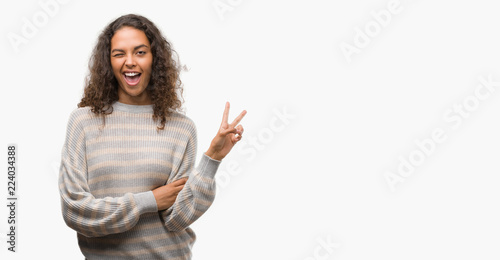 Fotografie, Obraz  Beautiful young hispanic woman wearing stripes sweater smiling with happy face winking at the camera doing victory sign