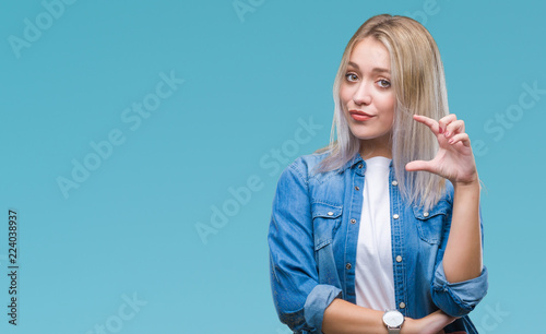 Young blonde woman over isolated background smiling and confident gesturing with hand doing size sign with fingers while looking and the camera Fototapet