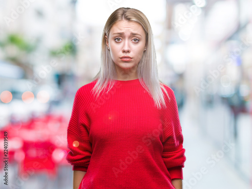 Foto Young blonde woman wearing winter sweater over isolated background depressed and worry for distress, crying angry and afraid
