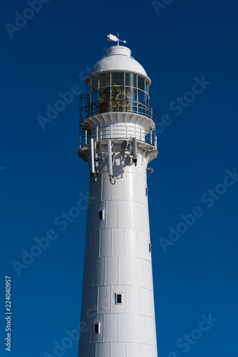Vertical close up of a lighthouse against a blue sky.