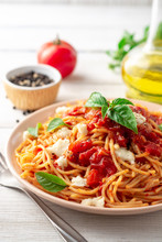 Spaghetti Pasta With Tomato Sauce, Mozzarella Cheese And Fresh Basil In Plate On White Wooden Background. Selective Focus.