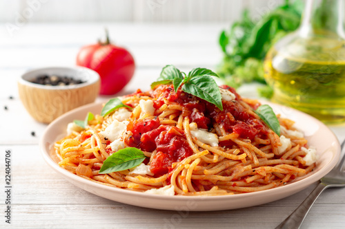 Spaghetti pasta with tomato sauce, mozzarella cheese and fresh basil in plate on white wooden background Fotobehang