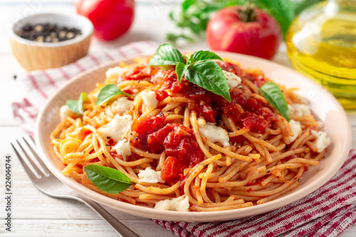 Fotografia Spaghetti pasta with tomato sauce, mozzarella cheese and fresh basil in plate on white wooden background