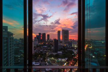 Glass window in room with view at beautiful sunset. Cityscape background image.
