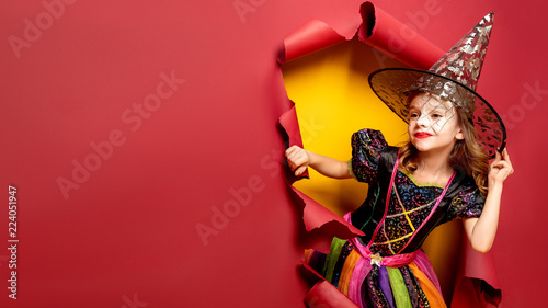 Happy Halloween. Laughing funny child girl in a witch costume of halloween looking and smiling through a hole of red, yellow paper background. Copyspace. 16 to 9 size