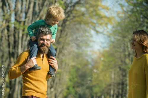 Active family play in park in their leisure time. Father give son piggyback ride in leisure park. All who wander are not lose