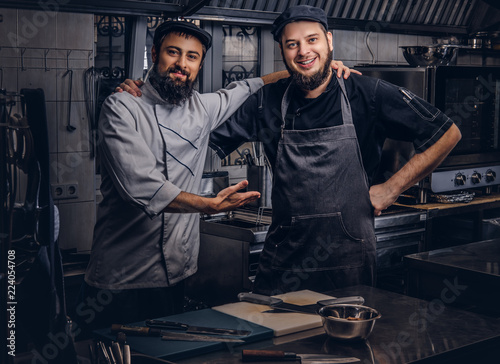 Fotografía Two happy bearded cooks friend dressed in uniforms and hats embrace while posing in kitchen