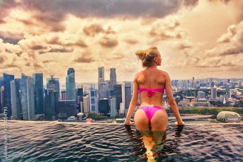 Tuinposter Aziatische Plekken Pretty woman admiring the sunset at the infinite pool. Singapore. Marina Bay Sands Hotel