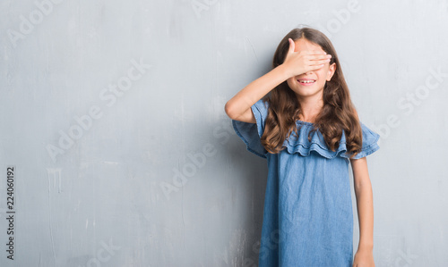 93b605f7eb01 Young hispanic kid over grunge grey wall smiling and laughing with ...