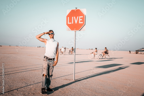 Fotografie, Obraz  Young man by the dream and live sign in the middle of a desert